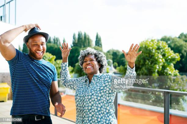 man and woman messing about and dancing - arms raised stock pictures, royalty-free photos & images