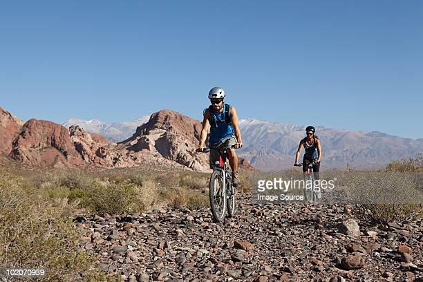 Man and woman mountain biking in rocky terrain