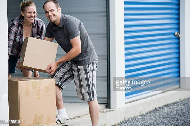 man and woman moving boxes at self storage unit - storage compartment stock pictures, royalty-free photos & images