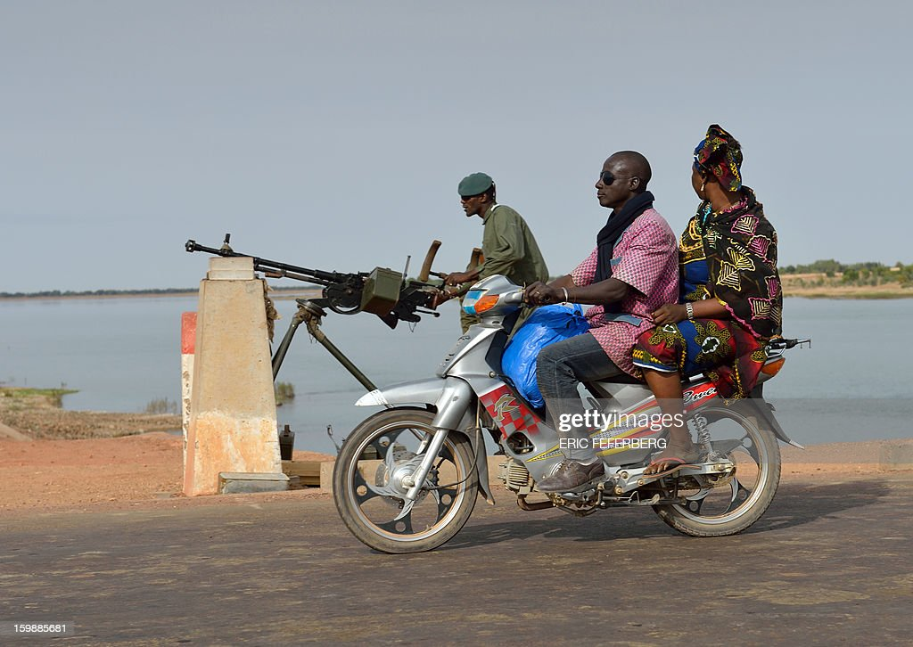 A man and woman on a scooter ride past a Malian soldier controlling a strategic bridge on the Niger river on January 22, 2013 near Markala, 270km North of Bamako. Mali's army chief today said his French-backed forces could reclaim the northern towns of Gao and fabled Timbuktu from Islamists in a month, as the United States began airlifting French troops to Mali.