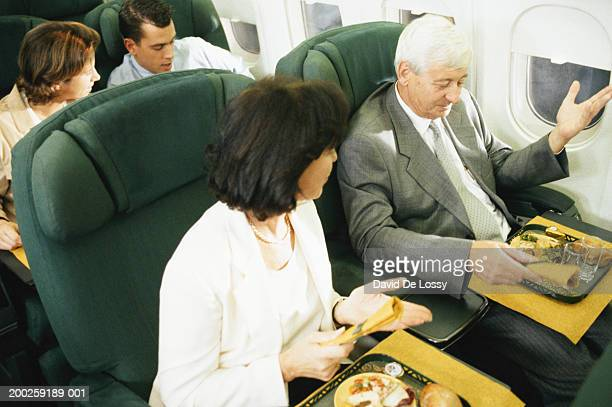 Man and woman on airplane having airline food