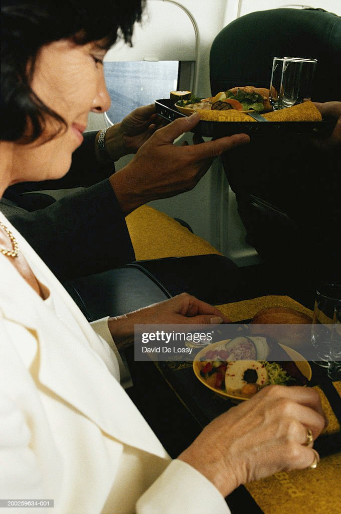 Man and woman on airplane having airline food : Stock Photo