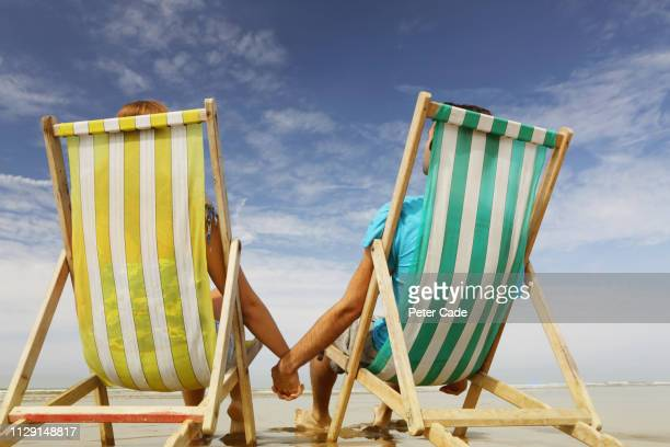 man and woman on beach in deckchairs - vacations stock pictures, royalty-free photos & images
