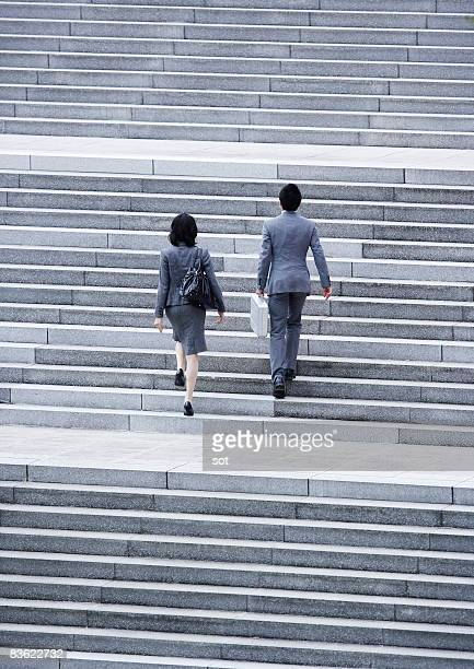 Man and woman on business going up the stairs,rear