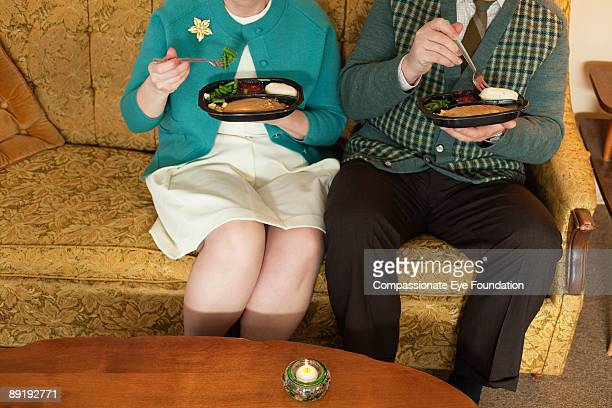 man and woman on couch holding tv dinners