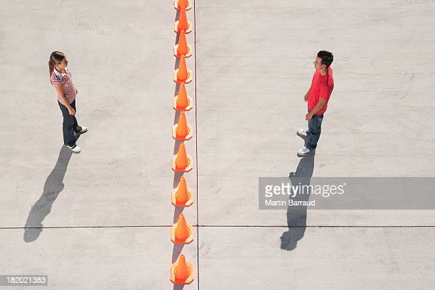 man and woman on either side of row of traffic cones looking back - ver stockfoto's en -beelden