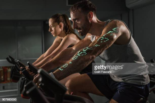 Man and woman on exercise bike with infographic