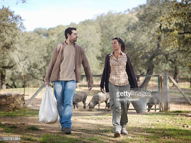 Man and woman on farm with cattle feed