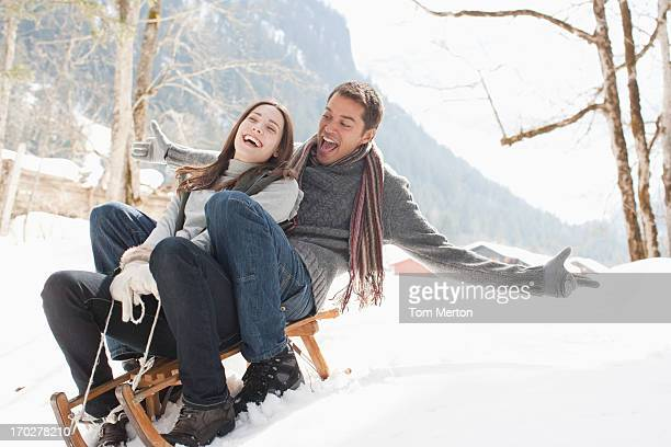 Man and woman on sled in snowy woods
