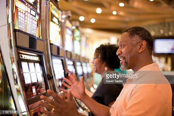 man and woman on slot machine - casino stock pictures, royalty-free photos & images