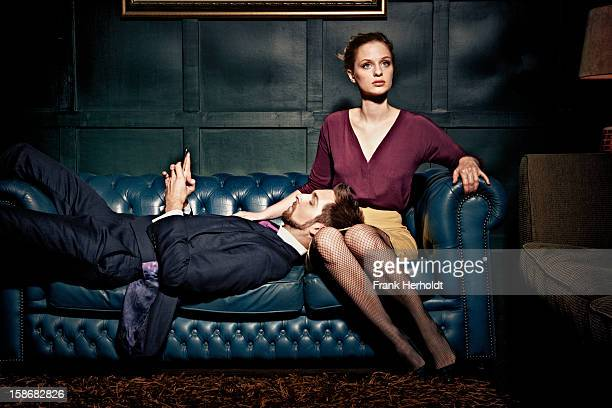Man and woman on sofa, man holding phone