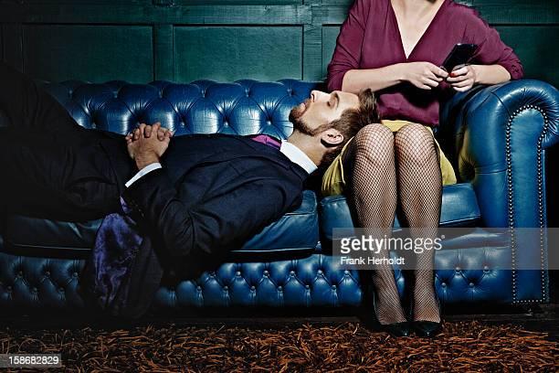 man and woman on sofa. woman holding phone - junge frau strumpfhose stock-fotos und bilder