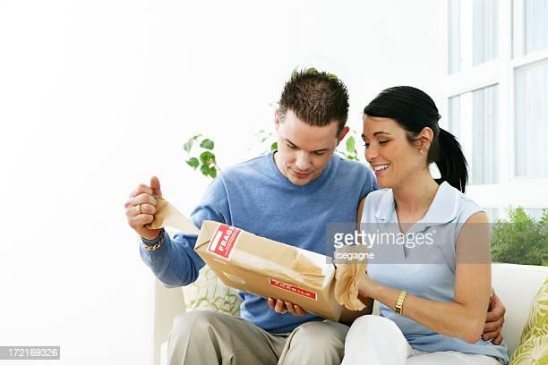Mann und Frau öffnen ein Paket