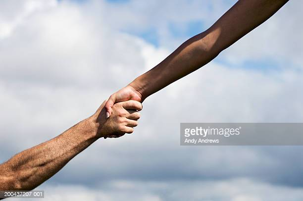 man and woman outdoors clasping hands, close-up - a helping hand stock pictures, royalty-free photos & images