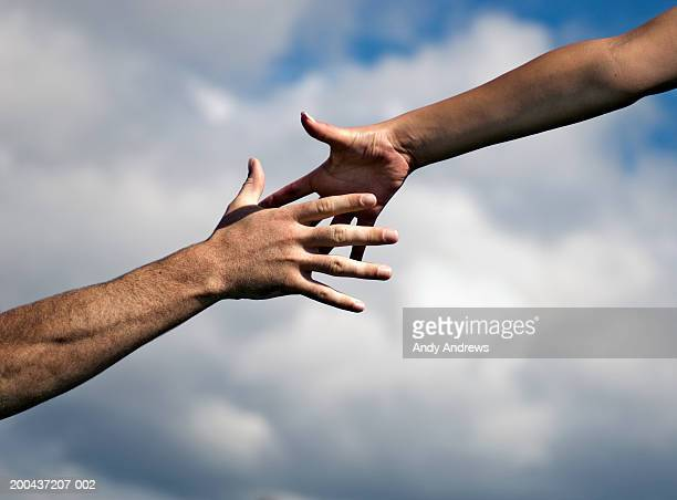 man and woman outdoors reaching out hands, close-up - weakness stock pictures, royalty-free photos & images