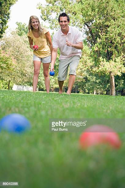 Man and Woman Outside Playing Bocce Ball