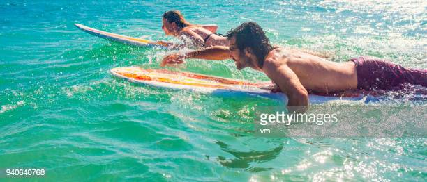 Man and woman paddling on surfboards
