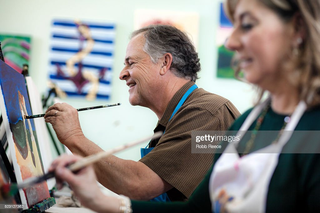 A man and woman painting fine art together in a studio : Stock Photo