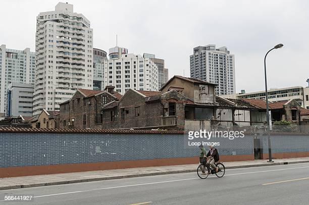 Man and woman passing in front of derelict buildings with new developments behind