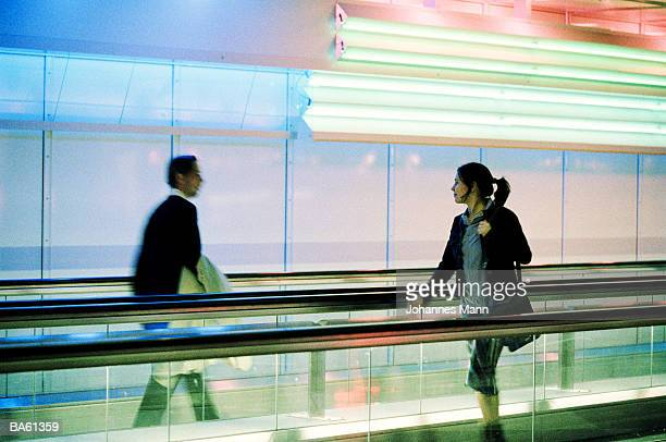 Man and woman passing one another on moving walkway (blurred motion)