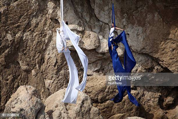 Man and woman performing acrobatics on Red Bull Cliff Diving World Series 2011 Lake Vouliagmeni Athens Greece May 22 2011 The divers jump from a 28m...