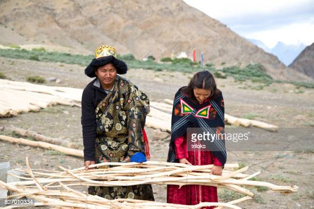 Man and woman picking up bunch of bamboo sticks