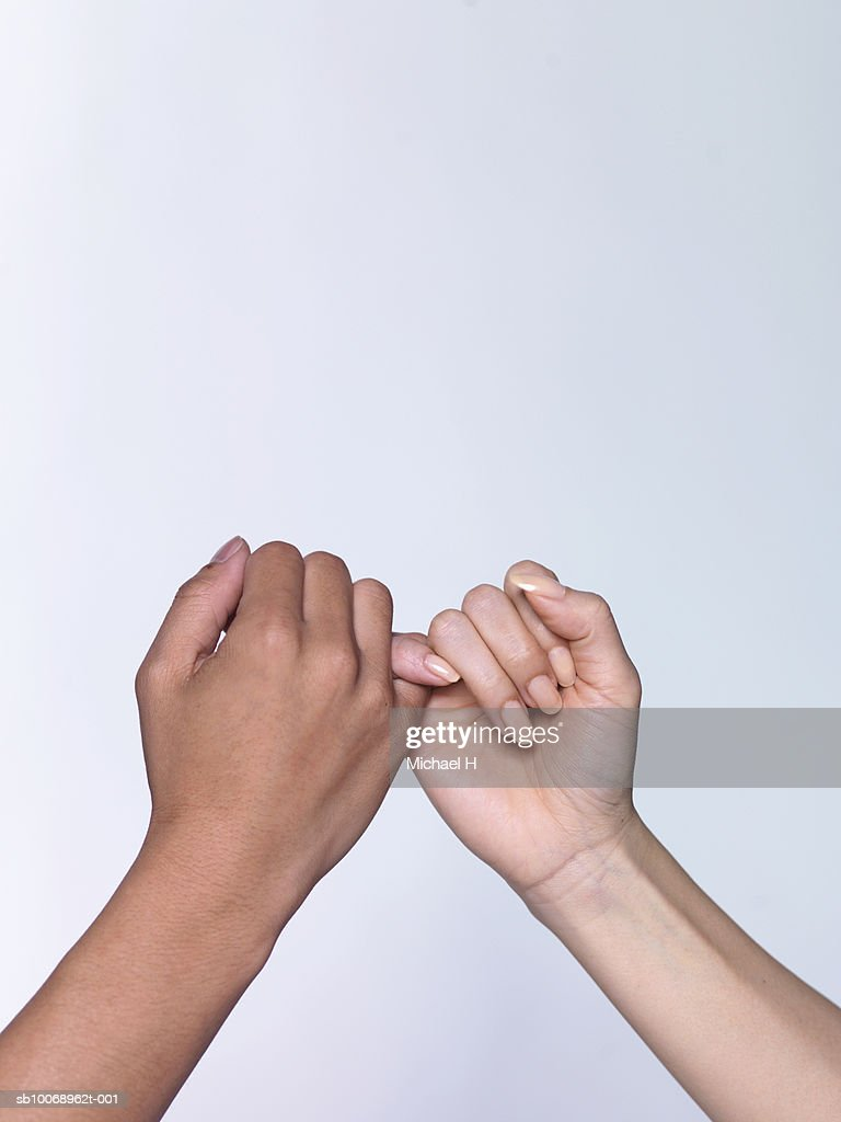Man and woman pinky-swearing, close-up of hands : Stock Photo
