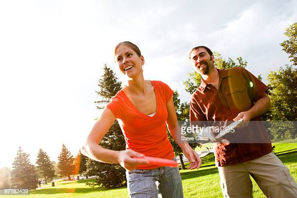 A man and woman play disk golf.