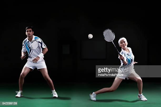 Man and woman playing badminton doubles at court