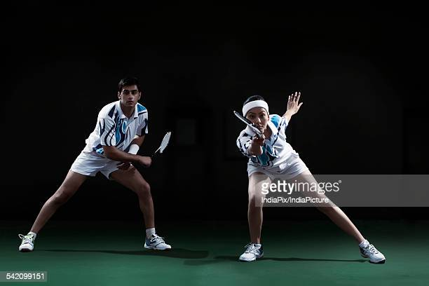 man and woman playing badminton doubles at court - badminton sport stock photos and pictures