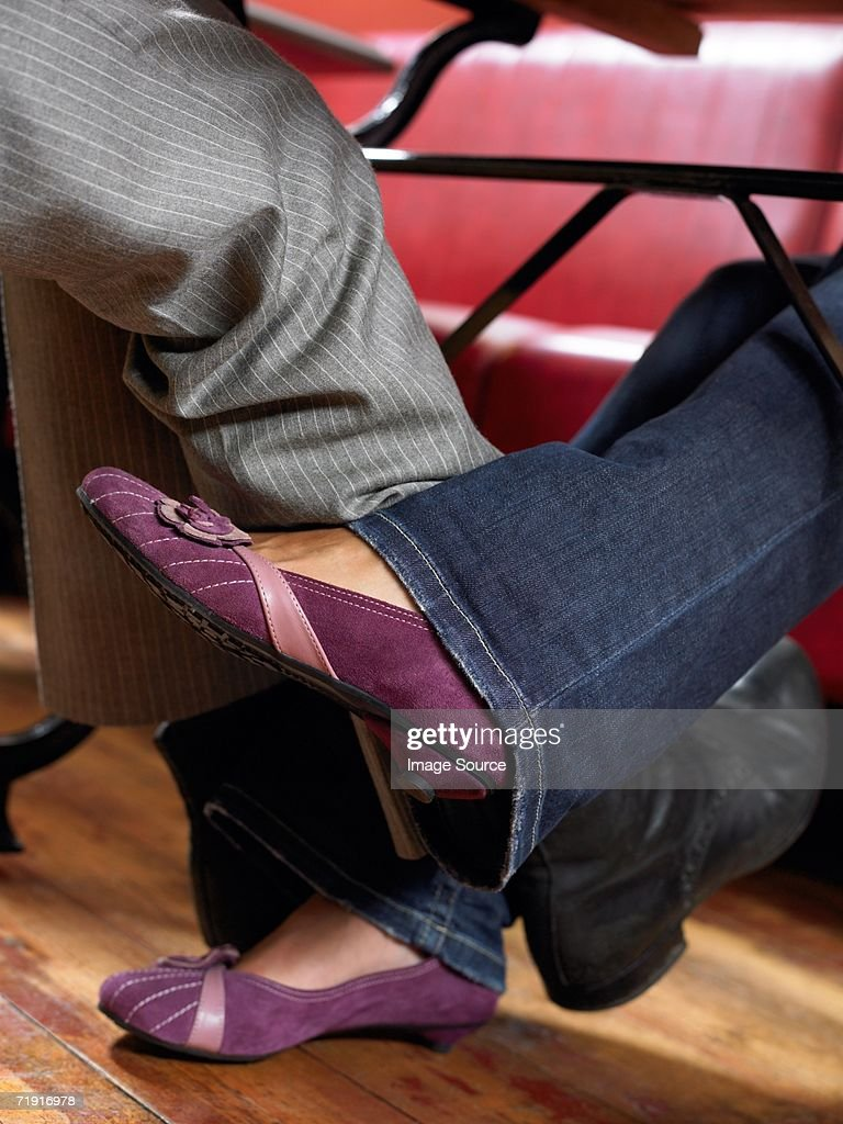 Man and woman playing footsie under table : Stock Photo