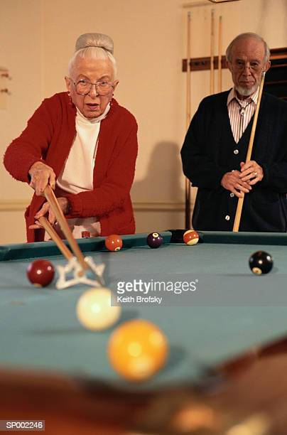 man and woman playing pocket billiards - old men playing pool stock pictures, royalty-free photos & images