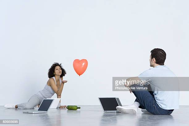 Man and woman playing spin the bottle with laptop computers
