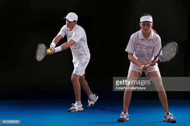 man and woman playing tennis doubles at court - doubles stock pictures, royalty-free photos & images