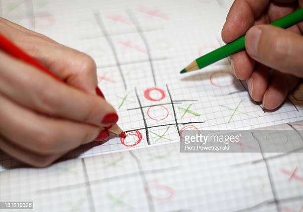 Man and woman playing Tic-tac-toe game.