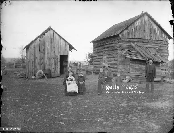 Man and woman posing sitting each holding a child in their lap and a young man girl and a boy holding a toy horn are posing standing Black River...