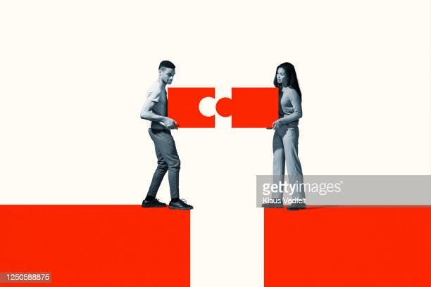 man and woman positioning orange puzzle pieces - solutions stock pictures, royalty-free photos & images