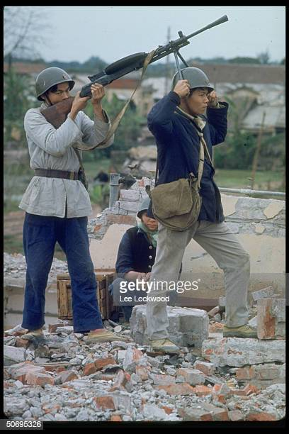 Man and woman practicing antiaircraft shooting w rifles during air raid drill on grounds of already heavily bombed factory