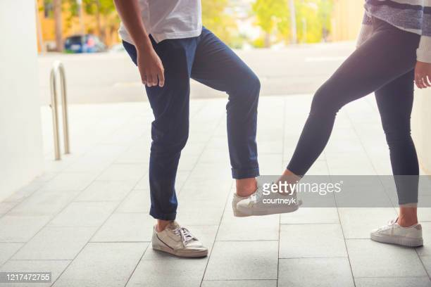 man and woman practicing social distancing outdoors. - elbow bump stock pictures, royalty-free photos & images