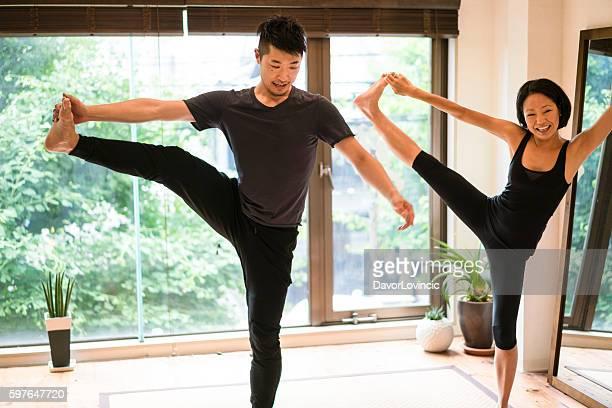 Man and woman practicing yoga, dandayamana pose in studio