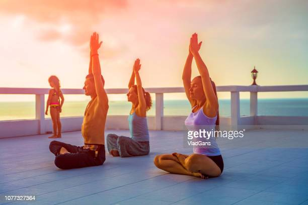 Man and Woman practicing yoga on the beach