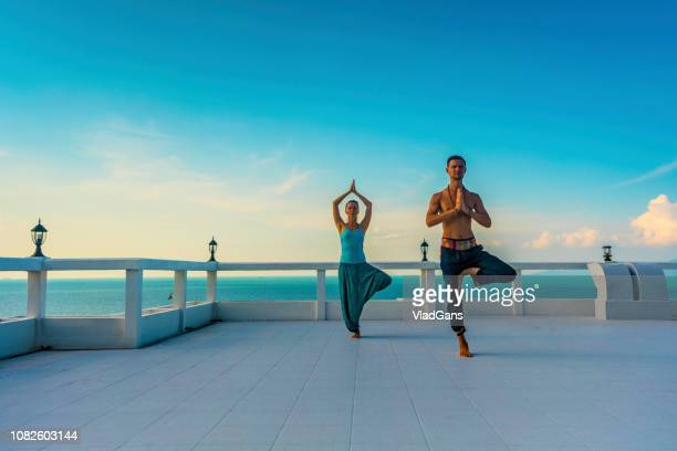 man and woman practicing yoga - tree position stock photos and pictures