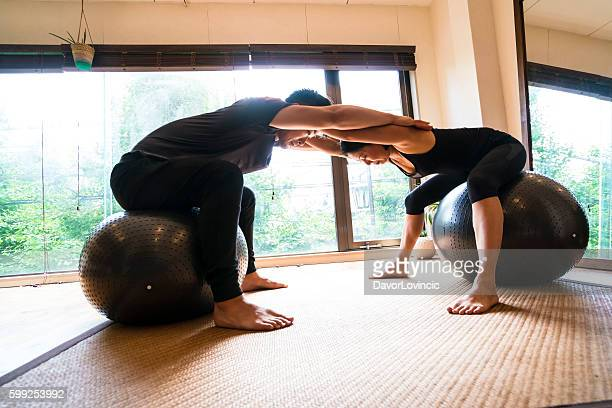 Man and woman practicing yoga with ball in Kyoto studio