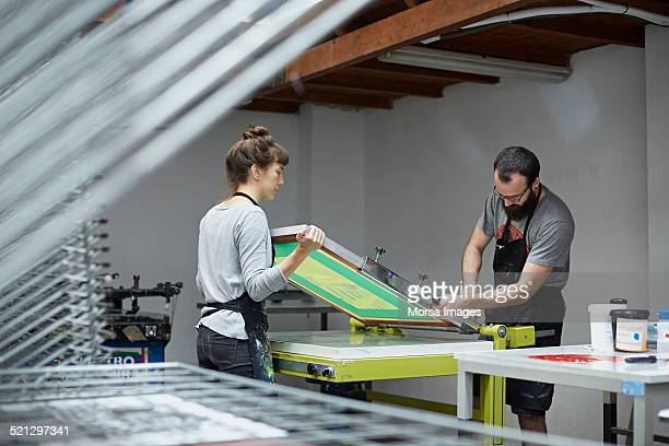 Man and woman preparing a screen to print