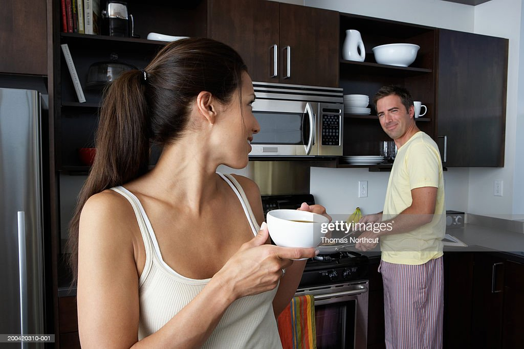 Man and woman preparing breakfast and smiling at one another : Stockfoto