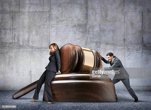 man and woman pushing in opposite directions against large gavel - lawsuit stock pictures, royalty-free photos & images