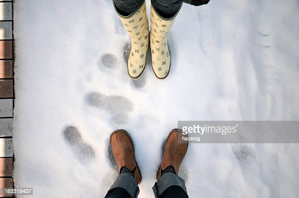 Man and woman put on their boots on the snow.