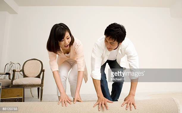 Man and woman puts down a rug on room