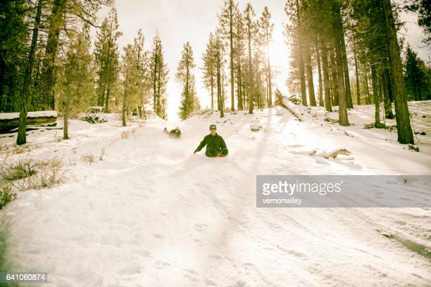 Man and woman racing sleds down a hill