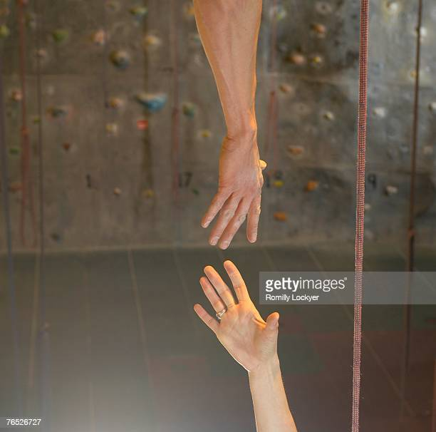 Man and woman reaching hands together at climbing centre